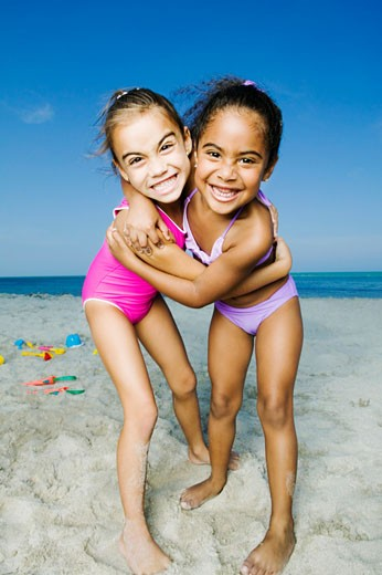 Portrait of two girls hugging each other on the beach : Stock Photo