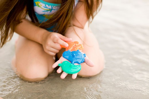 Mid section view of a girl playing with toys on the beach : Stock Photo