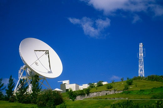 Side view of satellite dish amidst grass and shrubs, Devonshire, Bermuda : Stock Photo