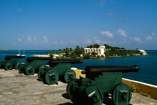 View of cannons with a fort seen in the background, Christiansvaern fort, St. Croix, U.S. Virgin Islands : Stock Photo