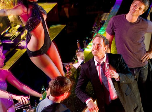 High angle view of three young men flirting with a dancer in a nightclub : Stock Photo