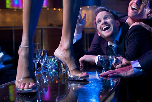 Two young men flirting with a dancer in a nightclub : Stock Photo