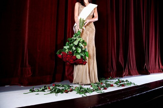 detail of winner of beauty contest on stage with bunch of red roses : Stock Photo