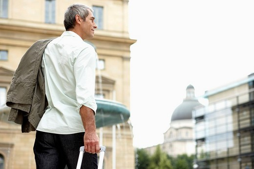 man walking through city street pulling carry_on : Stock Photo