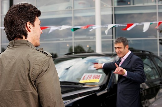 salesman at car dealer talking to customer : Stock Photo