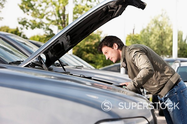 Stock Photo: 1669-14812 man at car dealer checking engine of car