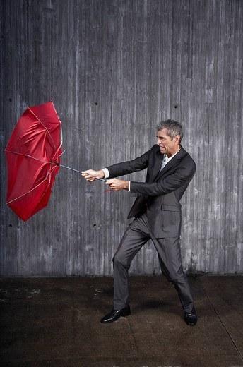 Stock Photo: 1669-15029 businessman trying to hold red umbrella in stormy weather