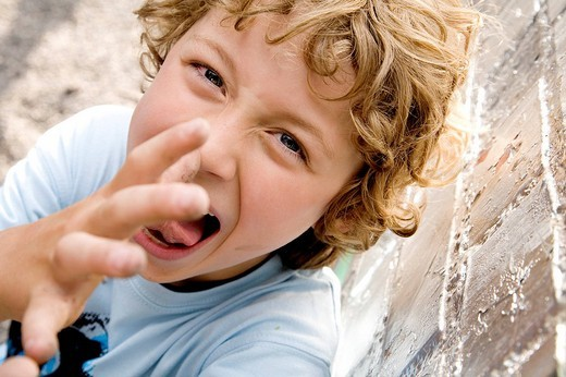 Stock Photo: 1669-15082 portrait of young boy thumbing his nose at camera