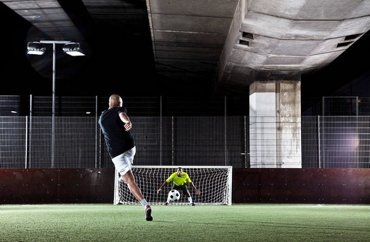 player shooting penalty at street football match : Stock Photo
