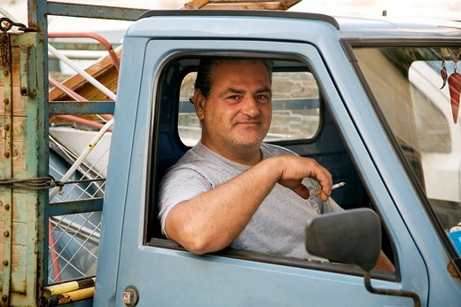 portrait of mature man looking out of his car in Italy : Stock Photo