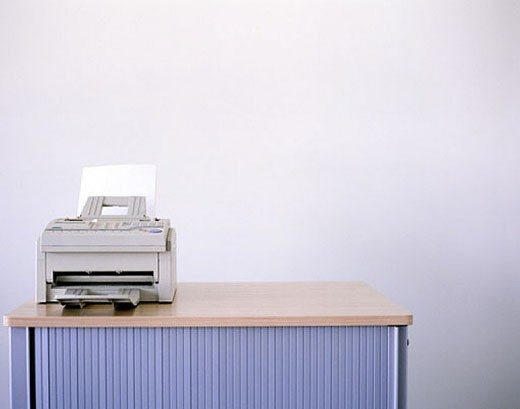 Stock Photo: 1669R-1002 grey faxmachine on horizontal office sideboard, white background