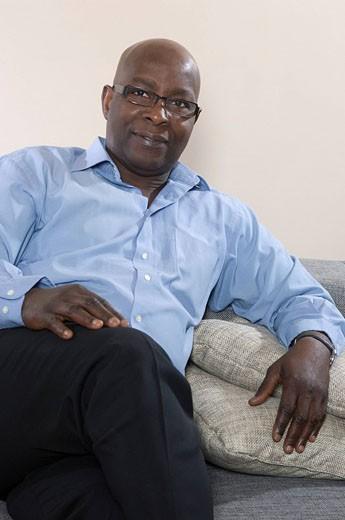 portrait of black businessman sitting on sofa : Stock Photo