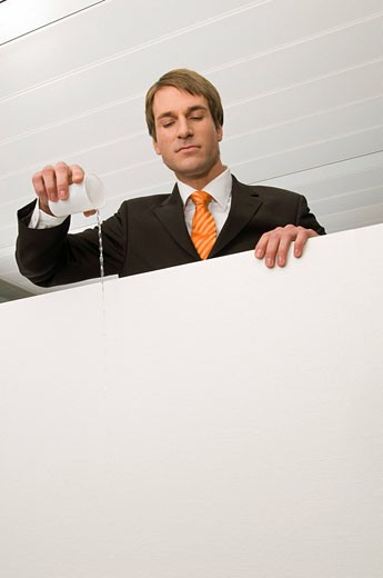 portrait of businessman pouring water from paper cup : Stock Photo