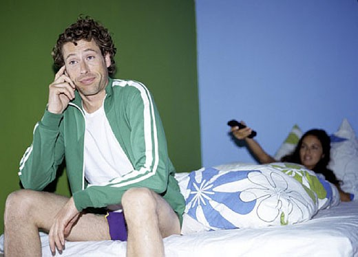 Stock Photo: 1669R-1047 man sitting on bed semidressed looking sceptical, woman in background with remote control