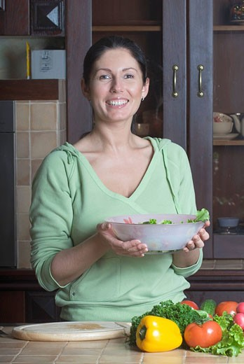 Stock Photo: 1669R-10902 portrait of woman in kitchen holding salad bowl