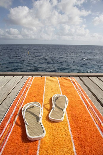 pair of flip flops and orange towel on pier in front of ocean : Stock Photo