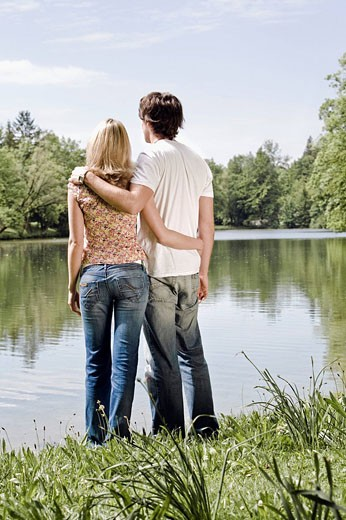 rear view of young couple standing by lake : Stock Photo
