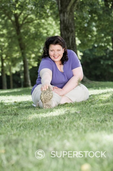 Stock Photo: 1669R-11156 overweight woman doing stretching exercises in park