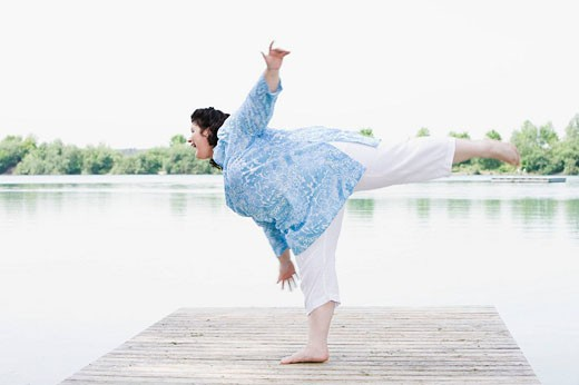 overweight woman doing stretching exercises on pier by lake : Stock Photo