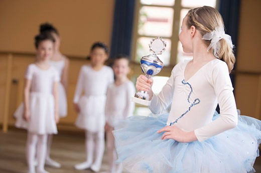 Stock Photo: 1669R-11238 young ballet dancer in front of group holding trophy
