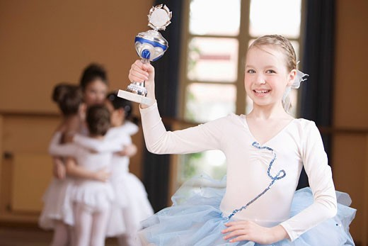 young ballet dancer in front of group holding trophy : Stock Photo