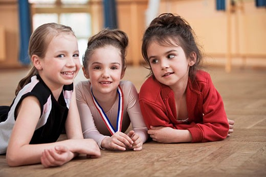portrait of three young ballet dancers lying on floor : Stock Photo