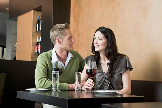 young couple sitting at restaurant with glasses of red wine : Stock Photo