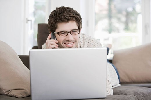 portrait of young man working at home with laptop computer and talking on telephone : Stock Photo