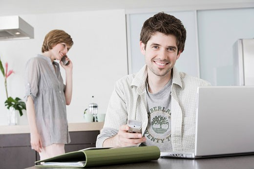portrait of man working from home with woman talking on telephone : Stock Photo