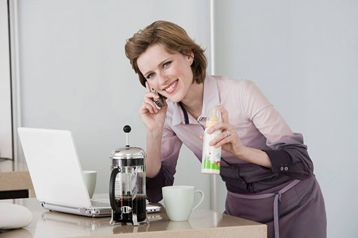 young woman at morning talking on telephone holding baby bottle and working with computer : Stock Photo