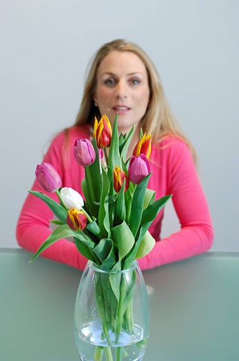portrait of blonde woman with vase of tulips : Stock Photo