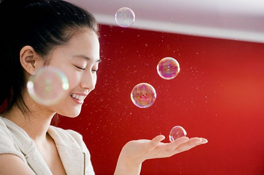 portrait of young japanese girl playing with soap bubbles : Stock Photo