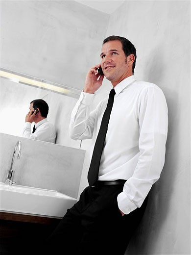 portrait of young businessman in front of mirror in bathroom talking on mobile phone : Stock Photo
