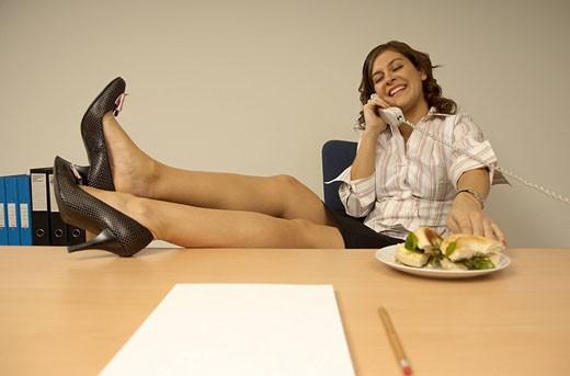 smiling secretary sitting at desk talking on the telephone with her legs up : Stock Photo