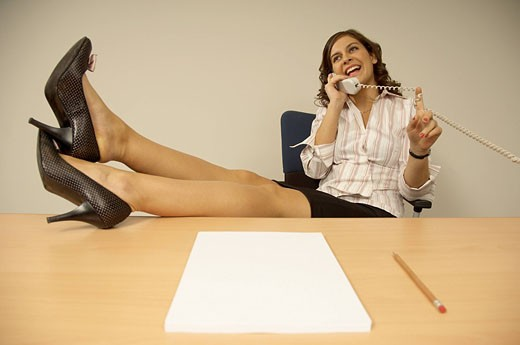 happy secretary sitting at desk with her feet up and talking on the telephone : Stock Photo