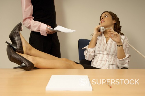 Stock Photo: 1669R-12264 businesswoman talking on telephone with colleague disturbing her
