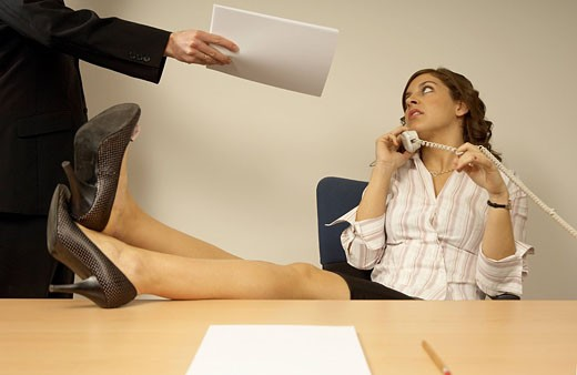 businesswoman talking on telephone with colleague disturbing her : Stock Photo