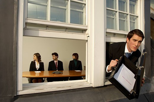 businessman leaving office building through window with briefcase full of confidential documents : Stock Photo