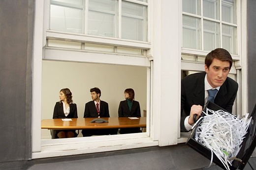 businessman leaving office building through window with briefcase full of shredded paper : Stock Photo