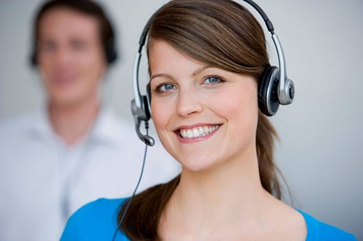 portrait of young female call center agent with male colleague in background : Stock Photo