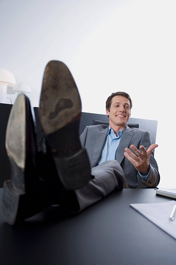 portrait of young entrepreneur sitting with his feet on desk : Stock Photo