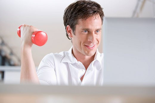 Stock Photo: 1669R-12508 businessman exercising with dumb bell while sitting at laptop computer