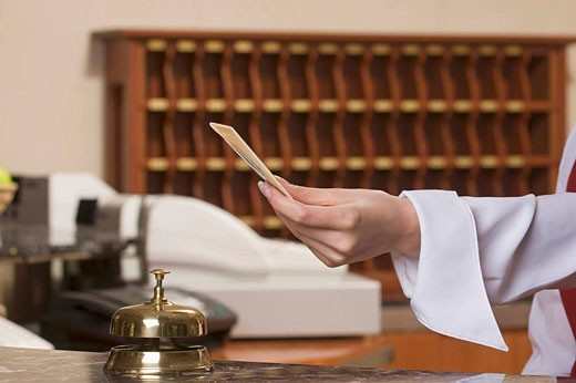 close_up of hotel receptionist holding key card : Stock Photo