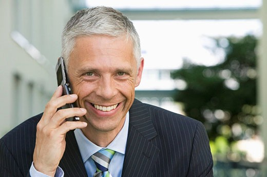 portrait of mature executive talking on mobile phone : Stock Photo
