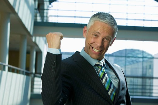 portrait of mature businessman celebrating success : Stock Photo