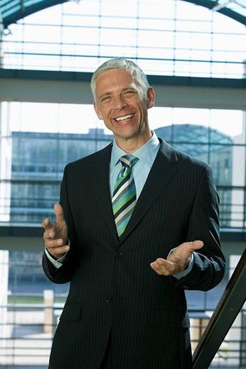 portrait of mature businessman making inviting gesture : Stock Photo