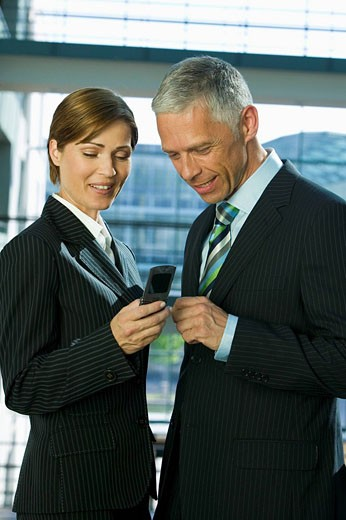 Stock Photo: 1669R-12736 portrait of mature businesswoman and male colleague looking at mobile phone