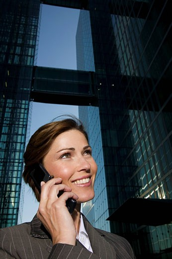 Stock Photo: 1669R-12766 low angle portrait of mature businesswoman talking on mobile phone in front of office building
