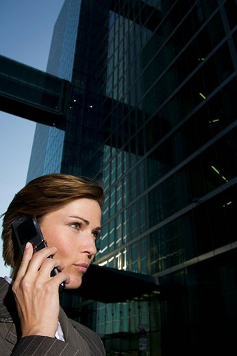 portrait of mature businesswoman talking on mobile phone in front of office building : Stock Photo