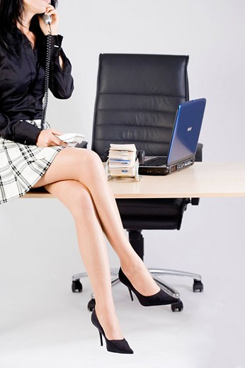 Stock Photo: 1669R-13028 detail of secretary sitting on desk and talking on telephone